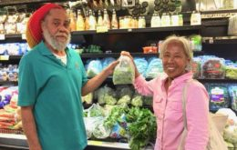 Starfish Market produce clerk Leslie Lambertis and Josephine Roller put a fresh bag of St. John-grown greens on the shelf.. Image via the St. John Source.