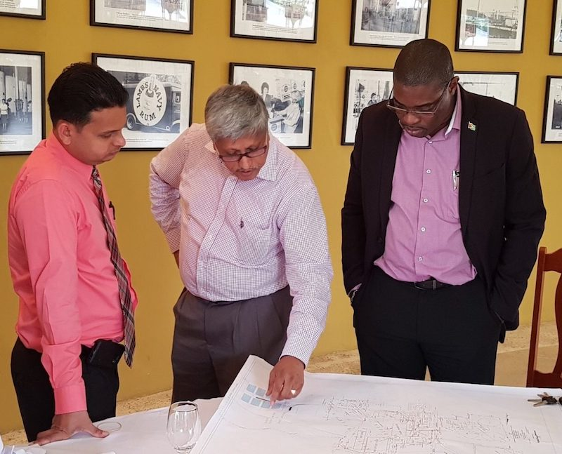 Minister Patterson looks at Diamond Land Use Map as DDL Chairman Komal Samaroo makes a point and DDL Finance Comptroller Vasuedo Singh looks on. Image: Guyana Ministry of Public Infrastructure via Stabroek News